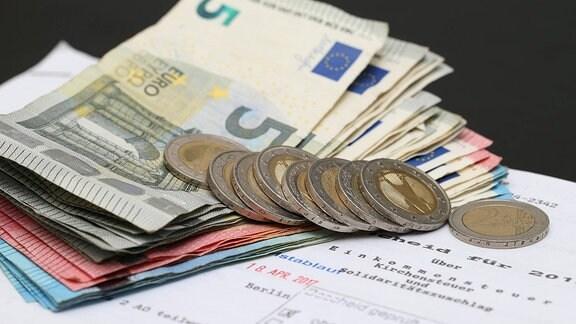 Geldscheine und Münzen auf einem Steuerbescheid