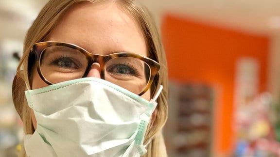 Eine Frau trägt einen Schutz über Mund und Nase