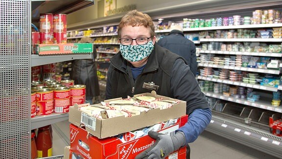 Eine Frau mit Mundschutz räumt in einem Supermarkt Regale ein