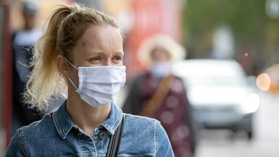 Eine Frau mit Behelfs- Mund und Nasenmaske in der Innenstadt von Jena.