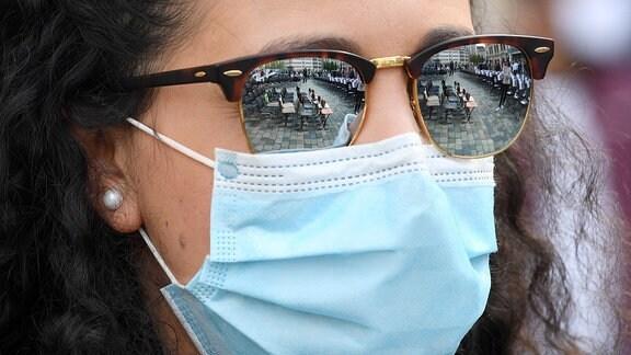 Frau mit Maske und Sonnenbrille