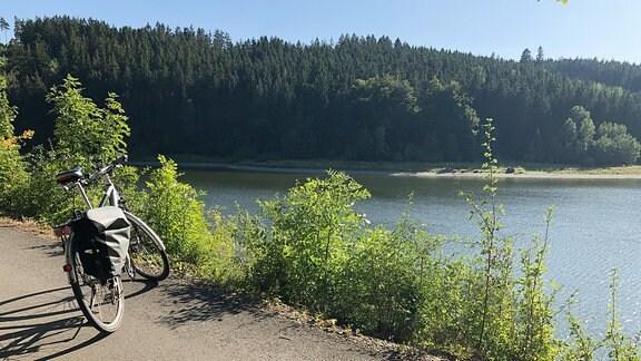 Ein Fahrrad steht auf einem Weg mit schönen Blick auf einen See und Wald.