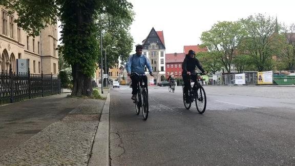 Zwei Radfahrer fahren nebeneinander auf einer Straße in Erfurt