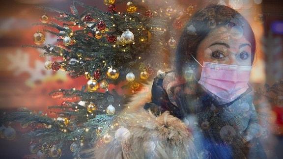Eine junge Frau mit Nasen-Mundschutz vor einem geschmückten Weihnachtsbaum.