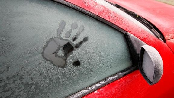 Ein Handabdruck auf einer gefrorenen Autoscheibe.