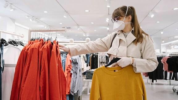 junge Frau mit Maske beim Shoppen