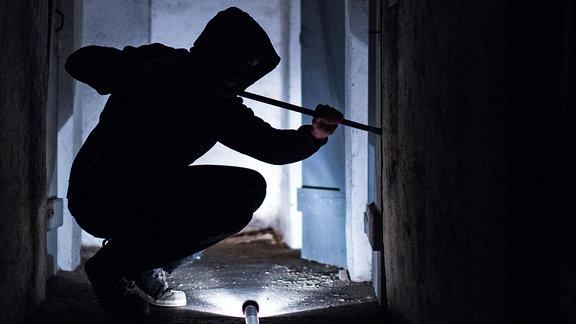 Ein fiktiver Einbrecher hebelt mit einem Brecheisen eine Tür im Keller eines Wohnhauses auf.