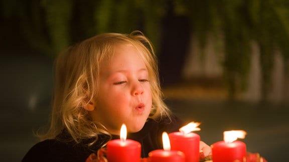 Ein Kleines Mädchen pustet die Kerzen am Adventskranz aus.