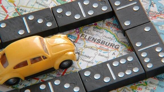 Dominosteine und Spielzeugauto auf einer Autokarte von Flensburg