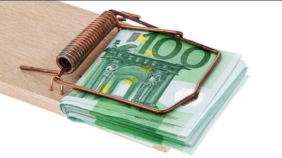 ein Bündel 100-Euro-Scheine ist in einer Mausefalle eingeklemmt