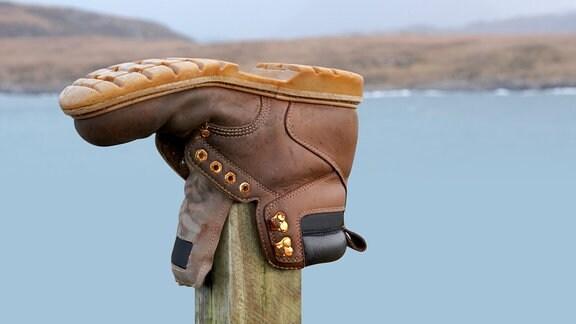 Ein Wanderstiefel steckt auf einem Pfahl. Im Hintergrund ist ein See zu sehen.