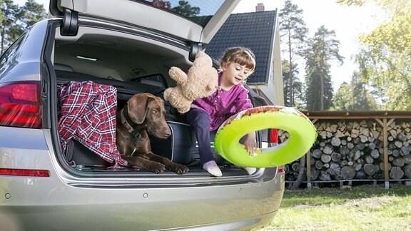 Ein kleines Mädchen spielt in einem beladenen Pkw-Kofferraum neben einem Hund.
