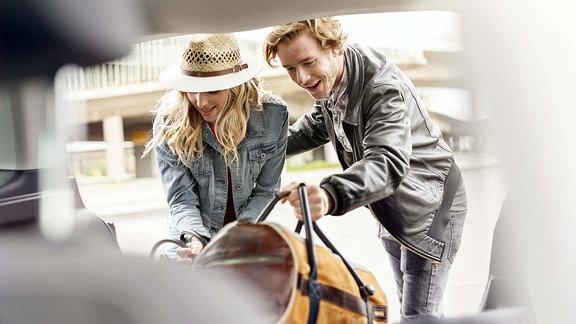 Ein Paar belädt den Kofferraum eines Autos.