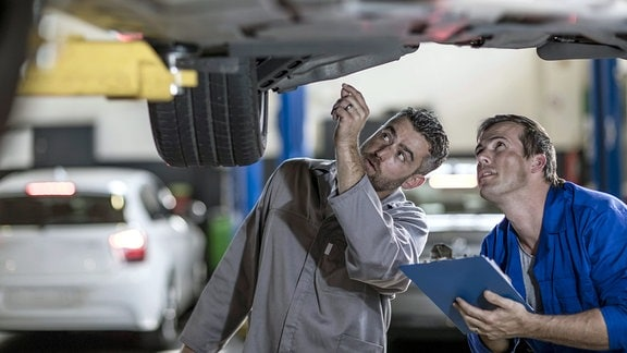Zwei Automechaniker in einer Werkstatt, die gemeinsam das Auto untersuchen.