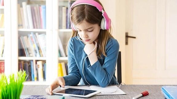 Kleines Mädchen, das Hausaufgaben mit Kopfhörern und digitaler Tablette tätigt.