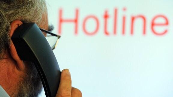 Illustration: Ein Mann hält einen Telefonhörer vor den Schriftzug «Hotline» auf einem Computermonitor.