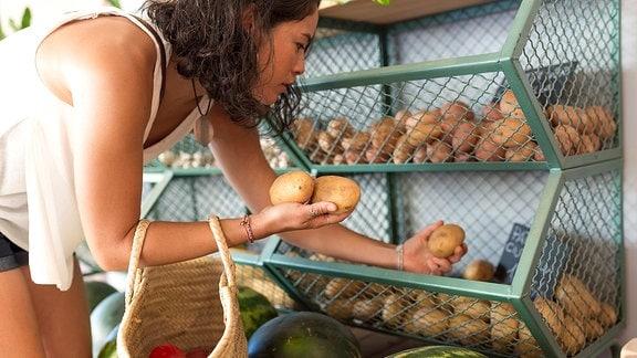 Eine junge Frau sucht in einem Laden Kartoffeln aus