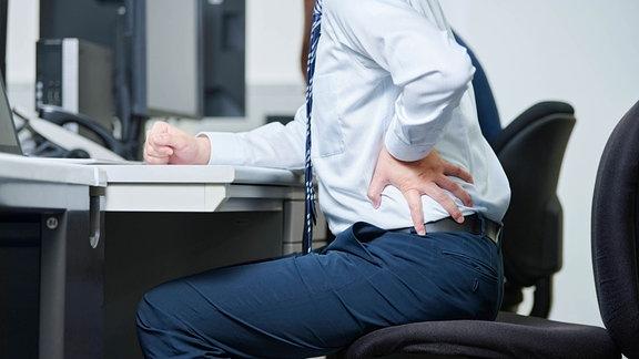 Mann im Büro mit Hüftschmerzen