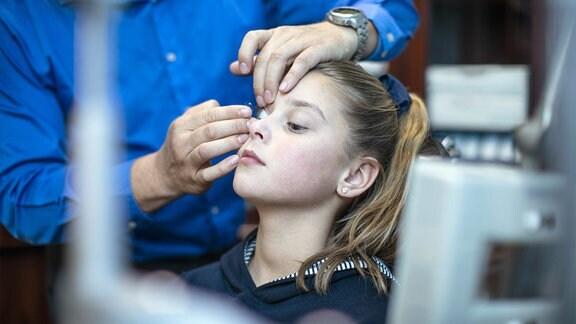 Optiker setzt Mädchen Kontaktlinse ein.
