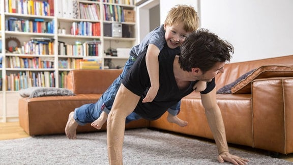 Ein Mann mit einem Kind auf dem Rücken macht Liegestütze