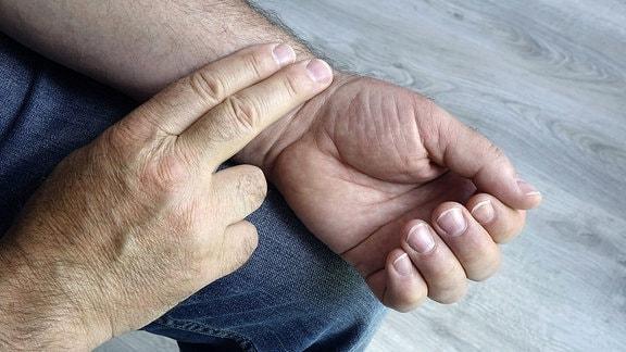Ein Mann fühlt am Handgelenk seinen Puls
