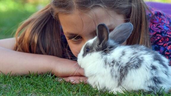 Mäödchen liegt zusammen mit einem Kaninchen auf einer Wiese