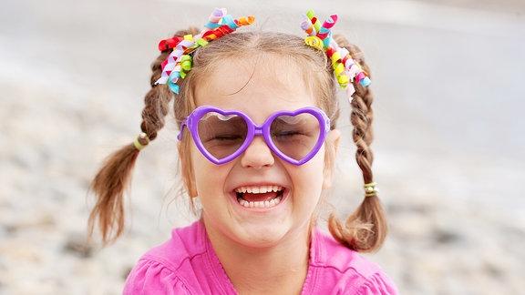 Ein Mädchen trägt eine Sonnenbrille.