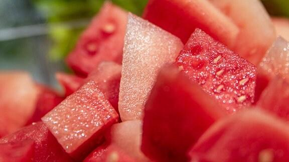 Melonenstücke zum Verzehr angerichtet, im Hintergrund Sellerie Wassermelone in Stücken