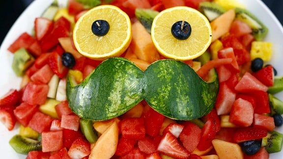 Melonensalat in einer Schüssel mit einem Gesicht aus Schale und Zitronenscheiben.