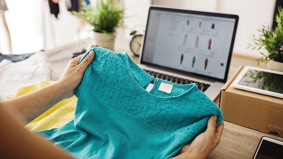 Eine Frau hält ein Oberteil vor einen Laptop.