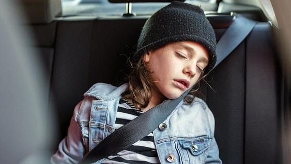 Ein Mädchen schläft auf der Rückbank eines Autos