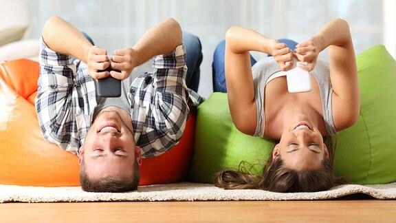 Eine Frau und ein Mann liegen auf dem Rücken. Beide schauen jeweils auf ihr Smartphone.