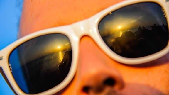Sonnenaufgang wird von Gläsern einer Sonnebrille reflektiert