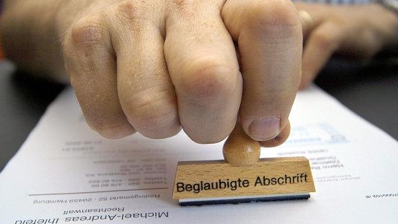 Beglaubigte Abschrift - Stempel wird auf eine Dokument gesetzt.