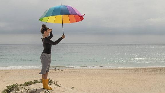 Frau mit langärmliger Kleidung und Sonnenschirm am Strand