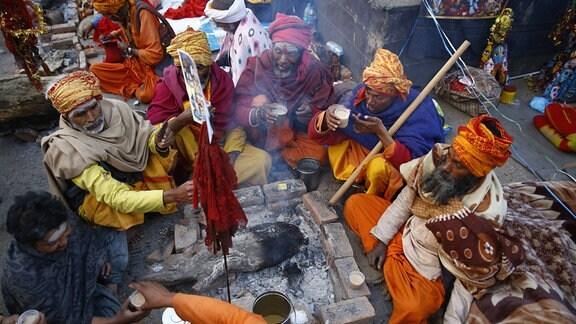 Sadhus oder heilige Männer sitzen nahe einem Feuer während Maha Shivaratri-Festivals an der Pashupatinath-Tempelprämisse in Kathmandu.