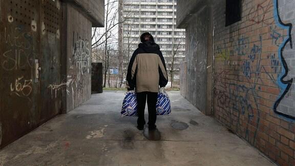 Symbolfoto zum Thema Armut in Deutschland : Eine Frau in einer Unterfuehrung an einer Plattenbau-Siedlung in Halle-Neustadt