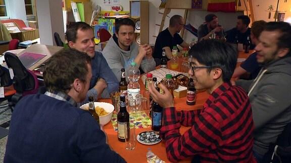 Eine Männerrunde sitzt an einem Tisch, redet und trinkt Bier