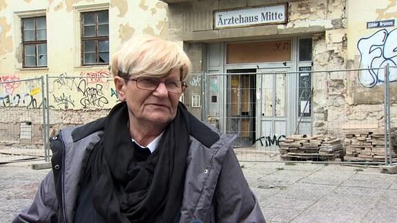 Eine Frau gibt vor einem verfallenen gebäude ein Interview