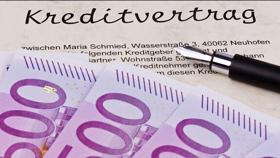 Auf einem Kreditvertrag liegen Geldscheine und ein Füllfederhalter.