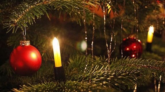 Rote Weihnachtsbaumkugeln, Kerzen und Lametta an einem Weihnachtsbaum