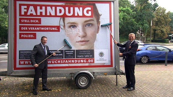 Der Rektor der Polizeifachhochschule Aschersleben, Knöppler, und Innenminister Stahlknecht bringen ein Plakat an, das für die Polizei werben soll