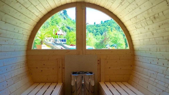 Blick durch die Fenster einer Fass-Sauna nach draußen ins Grüne