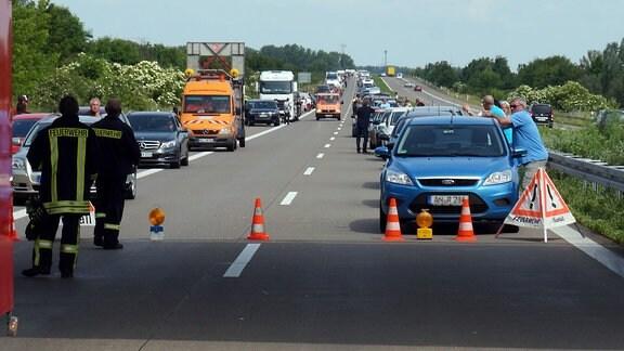 Auf einer Autobahn haben Autofahrer eine Rettungsgasse gebildet und warten hinter einer Absperrung neben ihren Pkws im Stau