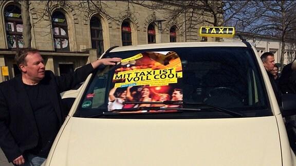 """Auf der Frontscheibe eines Taxis liegt ein Plakat mit der Aufschrift: Mit Taxi ist voll cool. Die Aktion """"Fifty-Fifty-Taxi"""" wird trotz gestiegener Preise fortgesetzt"""