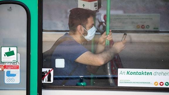 Ein Mann sitzt mit Mundschutz und Handy in einer Strassenbahn in Magdeburg.