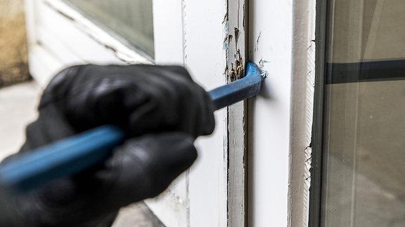 Eine behandschuhte Hand drückt ein Brecheisen in einen Türspalt