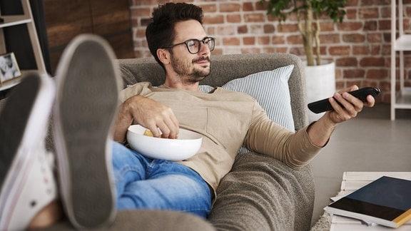 Mann liegt zufrieden auf Sofa und hält Schüssel mit Chips und Fernbedienung.