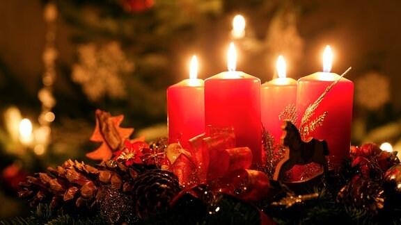 Vier rote Kerzen brennen auf einem Adventskranz