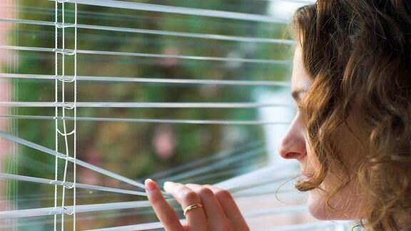 Eine Junge Frau am Fenster.
